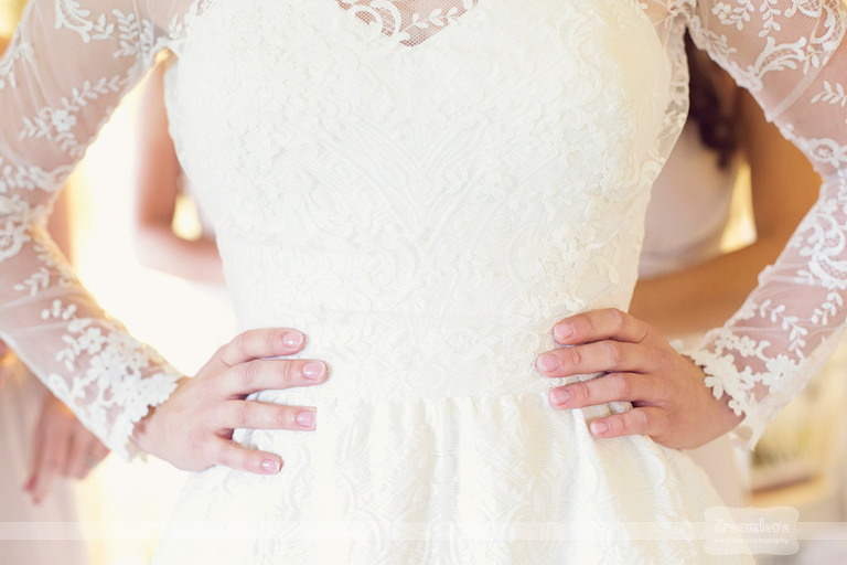 Closeup photo of a bride's lace dress while she gets ready for her wedding.