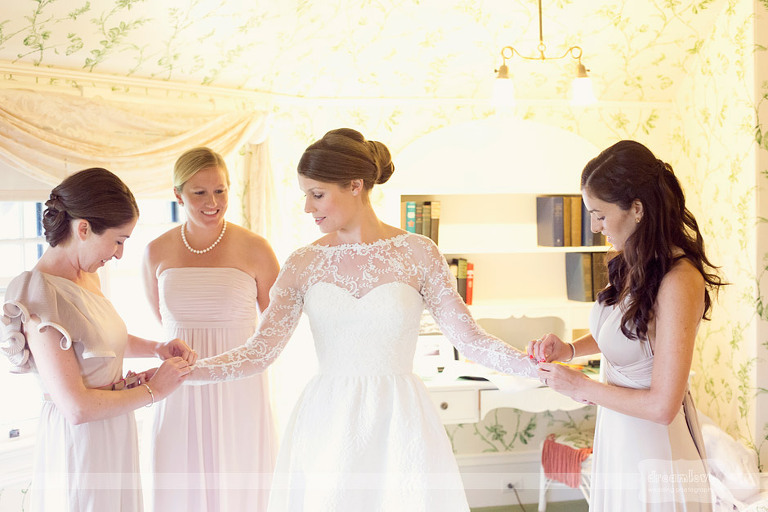 Bridesmaids help a bride with her dress while getting ready for a Shelburne Farms wedding.
