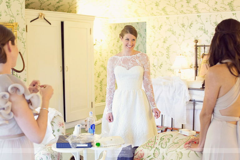 A bride smiles at her bridesmaids as she gets ready for her wedding at the Coach Barn at Shelburne Farms.