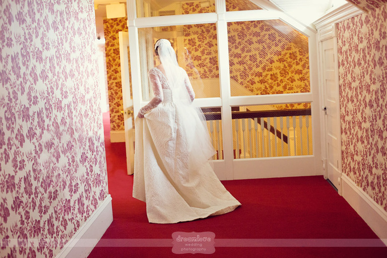 A bride walks down the hallways of an old Victorian house before a first look.
