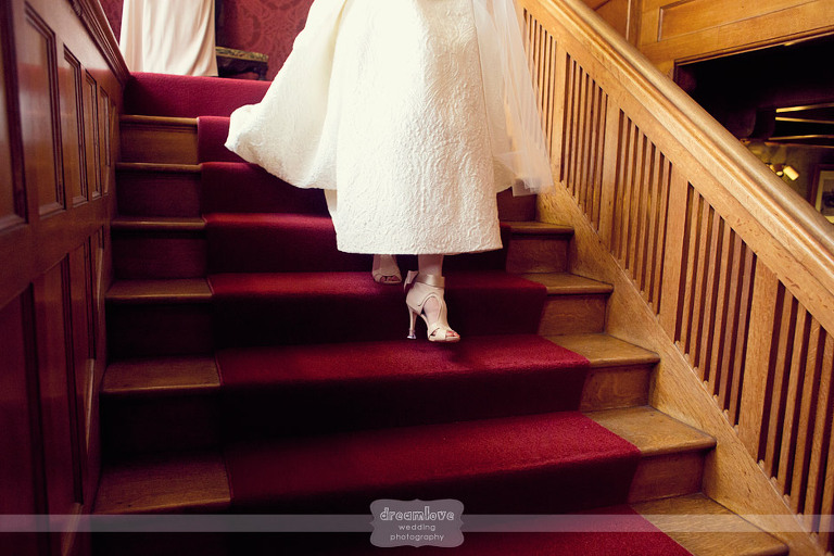 Detail of a bride's shoes as she walks down the stairs.