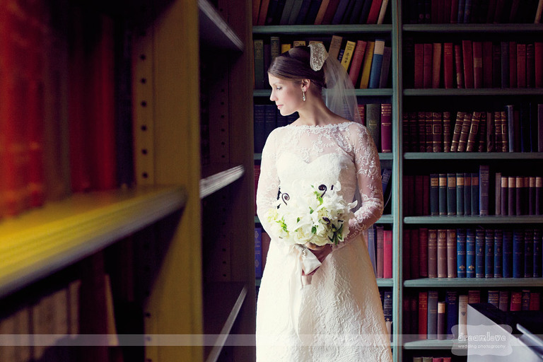 A bride looks out the window of an old library at Shelburne Farm in Vermont.