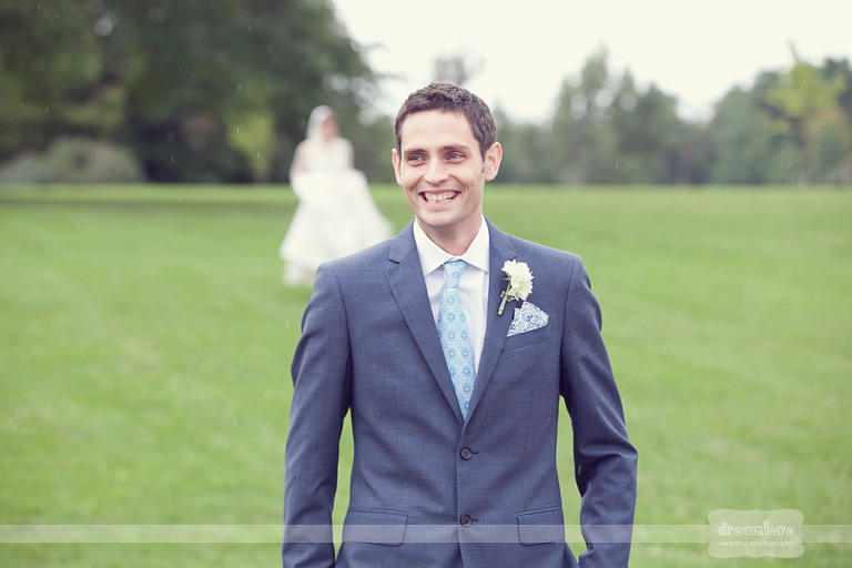 An excited groom smiles as his bride approaches for a first look at their elegant Shelburne Farms wedding at Coach Barn.