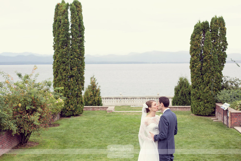 A bride and groom kiss in an Italian style garden with Lake Champlain in the background before their wedding at Shelburne Farms.