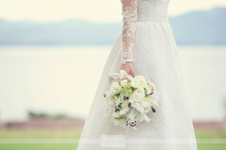 Detail of an elegant bridal bouquet and lace wedding dress with Lake Champlain in the background at Shelburne Farms.