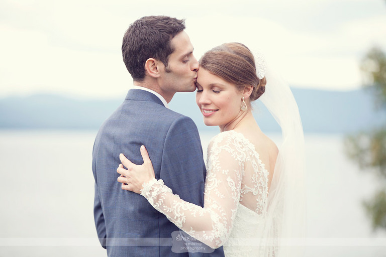 A bride and groom kiss in front of Lake Champlain at Shelburne Farms.