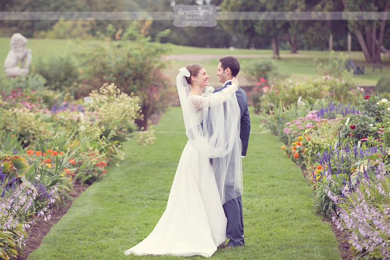Bride and groom smile at each other while taking pictures at Shelburne Farms.