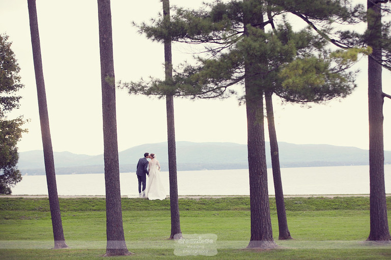 Nestled between tall pine trees, a bride and groom kiss with Lake Champlain in the background.