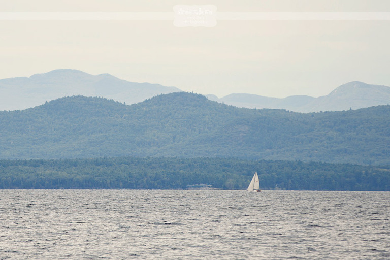 Looking out over Lake Champlain at a sailboat and mountains.