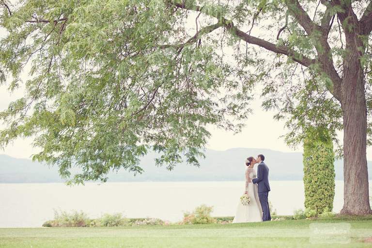 A couple kisses under a beautiful tree with Lake Champlain in the background before getting married at the Coach Barn in Shelburne, VT.