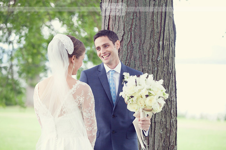Groom laughs with bride while holding bouquet as they stayed of the rain.