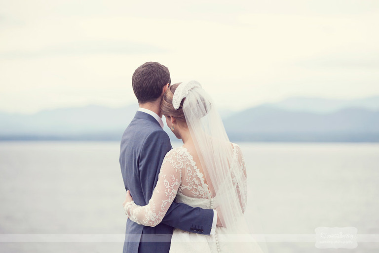 Bride and groom hug each other while looking out over Lake Champlain.