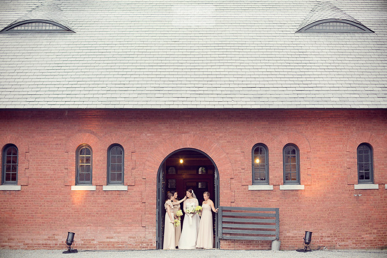 A bride and her bridesmaids wait underneath an arched doorway at the Coach Barn.