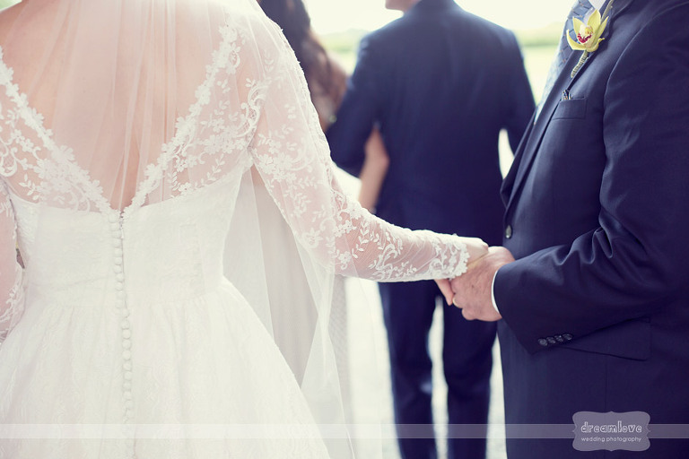 A bride holds her dad's hand before walking down the aisle at their elegant Coach Barn wedding at Shelburne Farms.