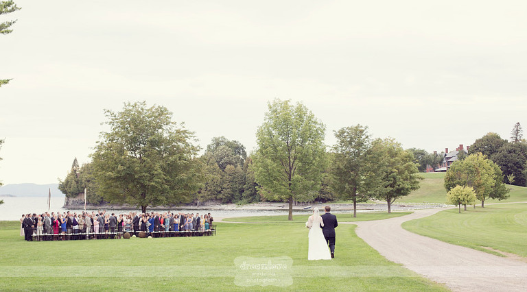 A bride and her father walk to a lakeside wedding ceremony at Shelburne Farms in Vermont.