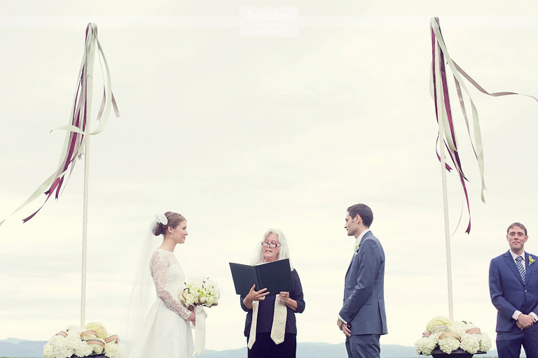 A bride and groom smile at their wedding ceremony next to Lake Champlain at Shelburne Farms.