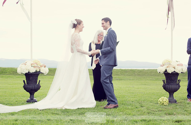 Bride and groom laugh after exchanging their rings at their wedding at Shelburne Farms.