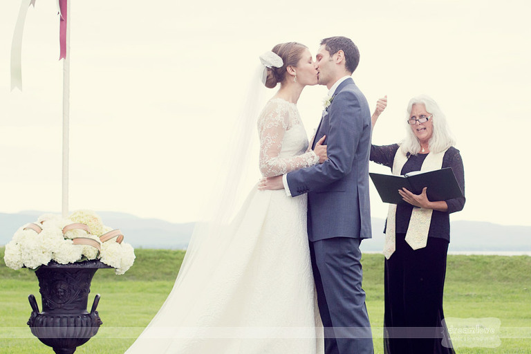 Bride and groom kiss during their ceremony at Shelburne Farms.