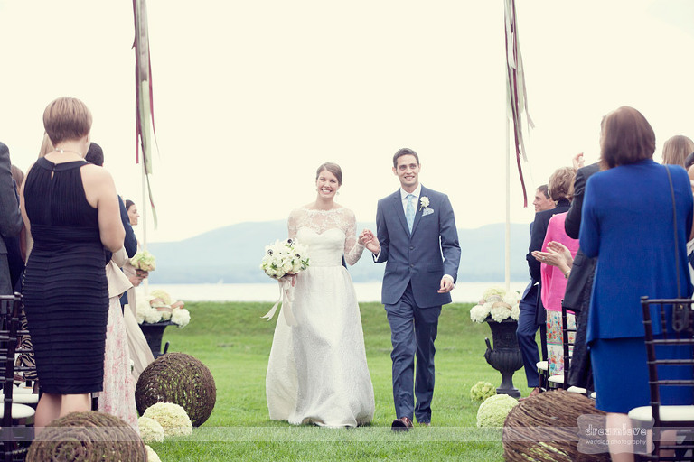 With Lake Champlain in the background, a bride and groom walk down the aisle after getting married at Shelburne Farms.