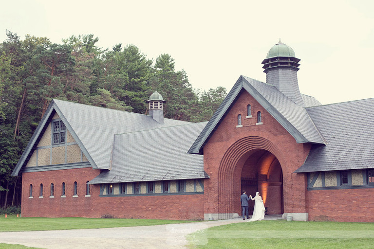 All by themselves, a bride and groom walk into the Coach Barn at Shelburne Farms in Vermont.