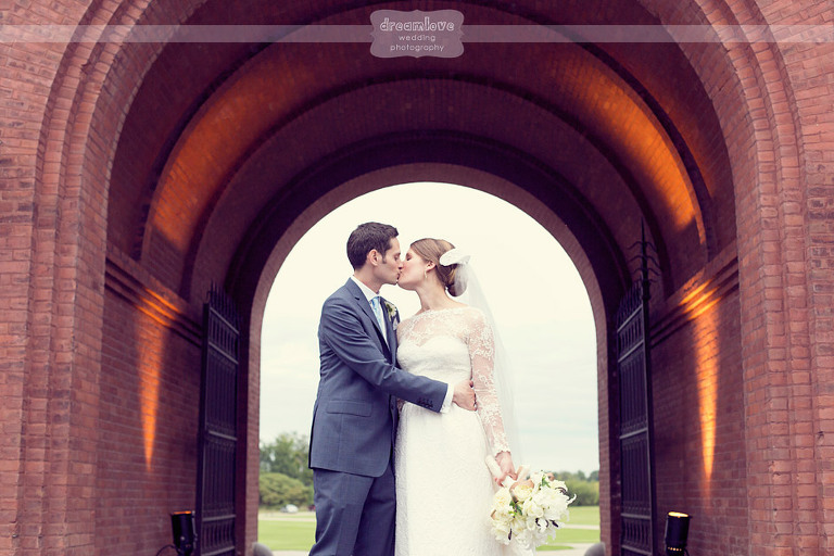 Bride and groom kiss underneath the archways at the Coach Barn.