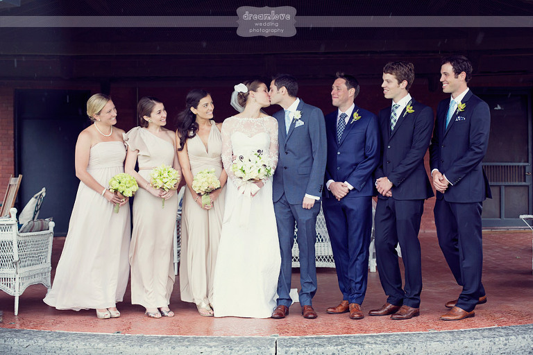 The wedding party smiles as the bride and groom kiss.