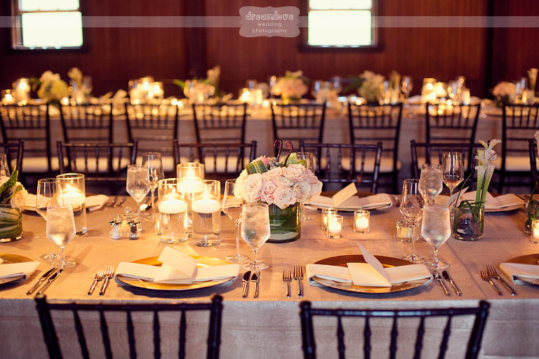 Elegant dinner tables with pink roses and floating candles at the Coach Barn at Shelburne Farms.