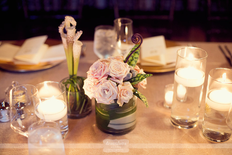Table centerpieces included pink roses and floating candles.