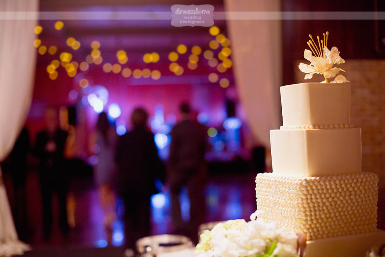 A box styled wedding cake with twinkle lights in the background.