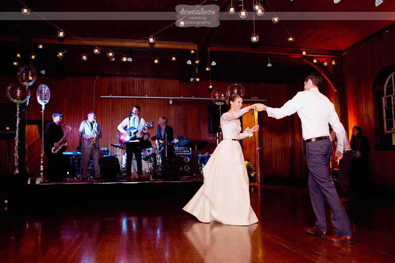 A bride and groom share their first dance during a reception at the Coach Barn at Shelburne Farms.