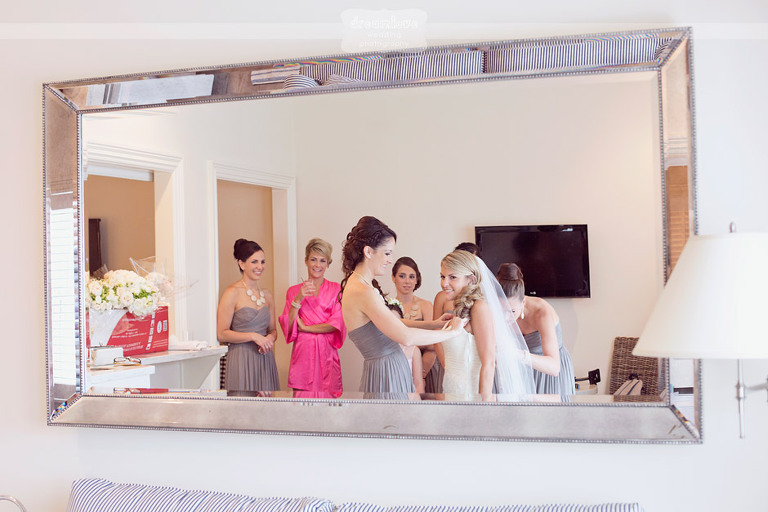 A bride looks into the mirror while getting ready for her Cape Cod wedding.