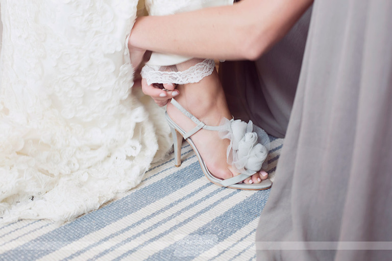 A detailed picture of a bride slipping on her wedding shoes.
