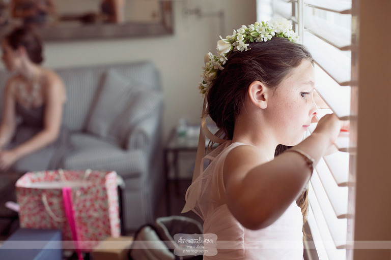 A flower girl peeks out the window as the wedding party gets ready for a Wychmere Beach Club wedding on Cape Cod.