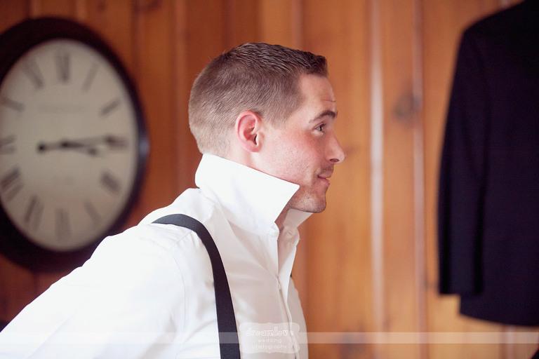 Groom puts on his suspenders before his Cape Cod wedding.