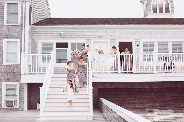 A bridal party walks down the steps before a summer wedding at the Wychmere Beach Club.
