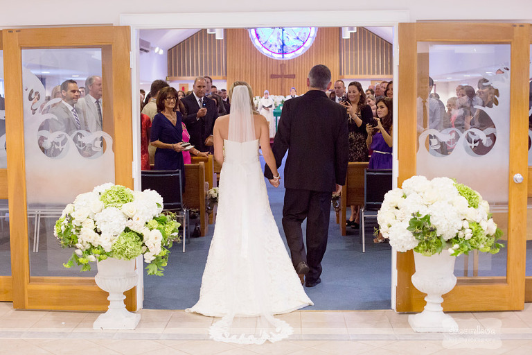Guests look on as a bride and her father walk down the aisle.