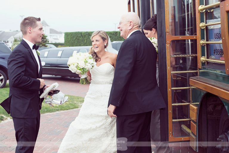 Bride and groom smile while getting off a trolly at the Wychmere Beach Club on Cape Cod.