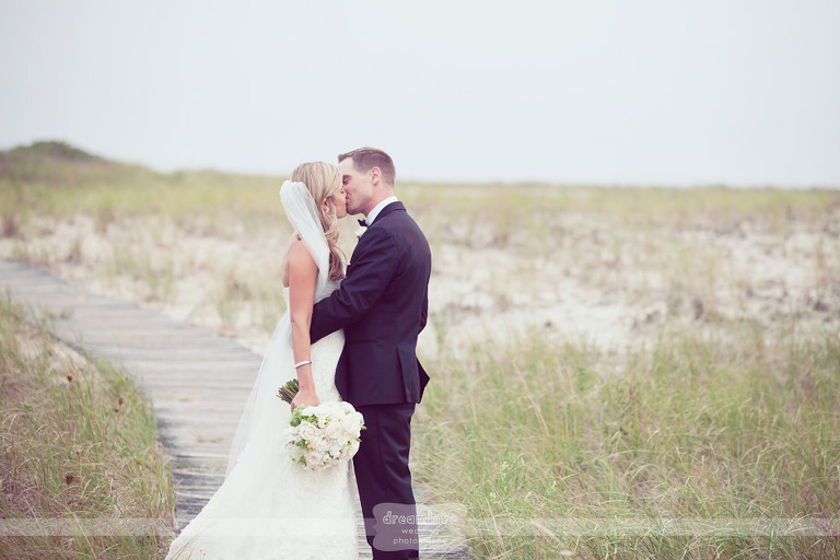 A couple kisses on the boardwalk out to the beach at the Wychmere on Cape Cod.