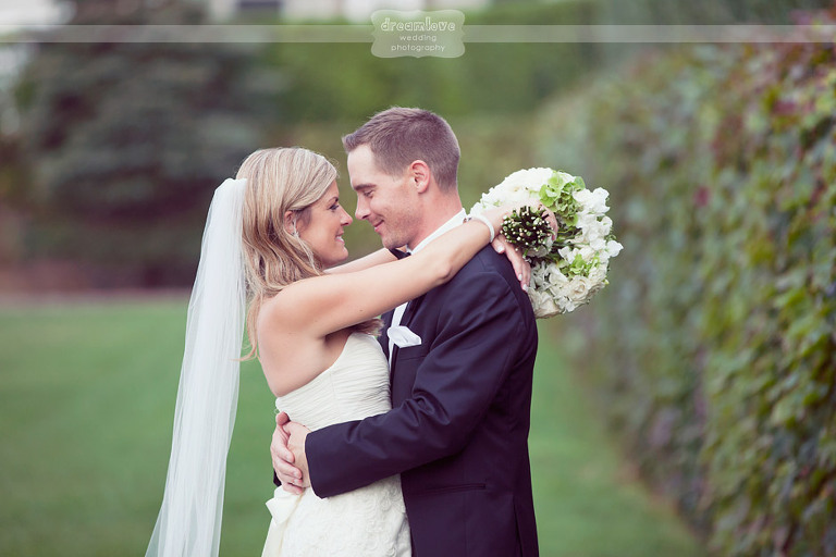 Smiling couple on their wedding day surrounded by the lush hedgerows at the Wychmere Beach Club.