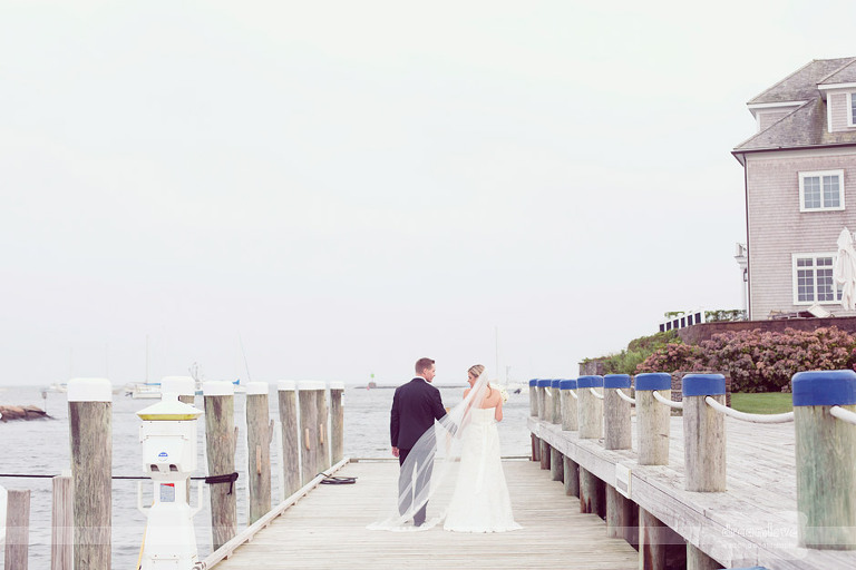 With the ocean in the background a bride and groom walk along with Wychmere's docks.