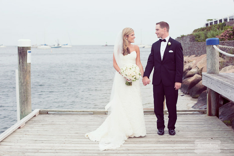 A young couple holding hands on the docks outside of the Wychmere Beach Club after getting married.