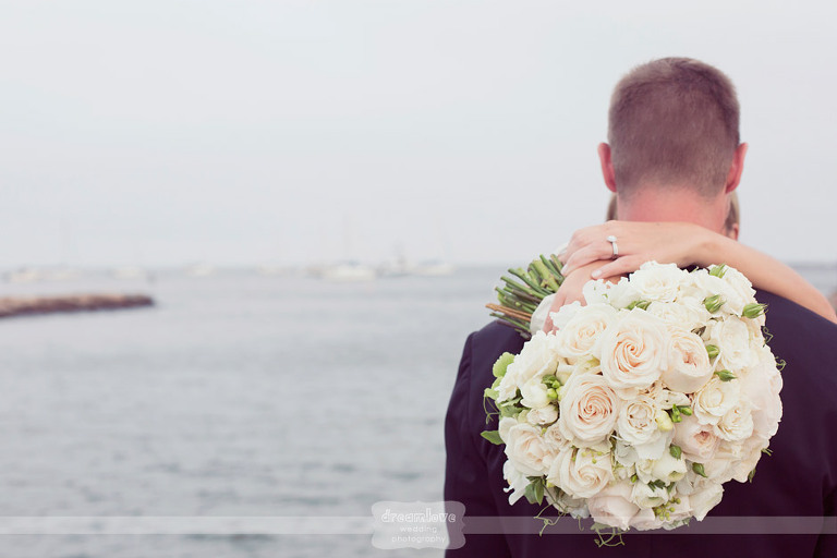 A detail of the bride's bouquet with the ocean in the background at the Wychmere Beach Club in Harwich, MA.