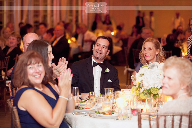 The grooms parents laugh during their son's wedding reception.
