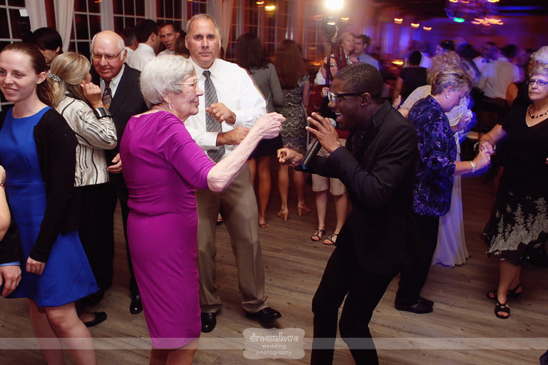 An older wedding guest dances with the singer from the band.