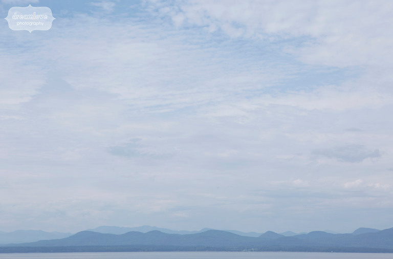stunning landscape with green mountain range over lake champlain from the shelburne farms wedding venue