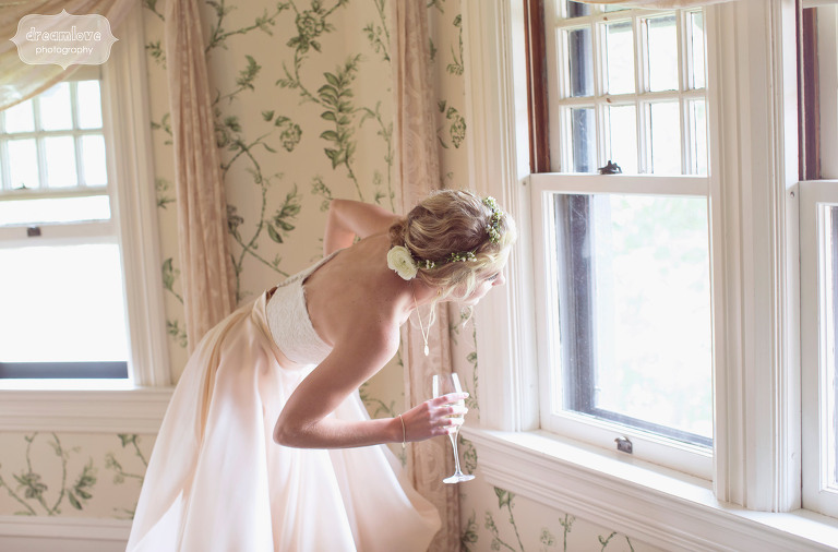 bride looks out window of shelburne farms estate while holding champagne