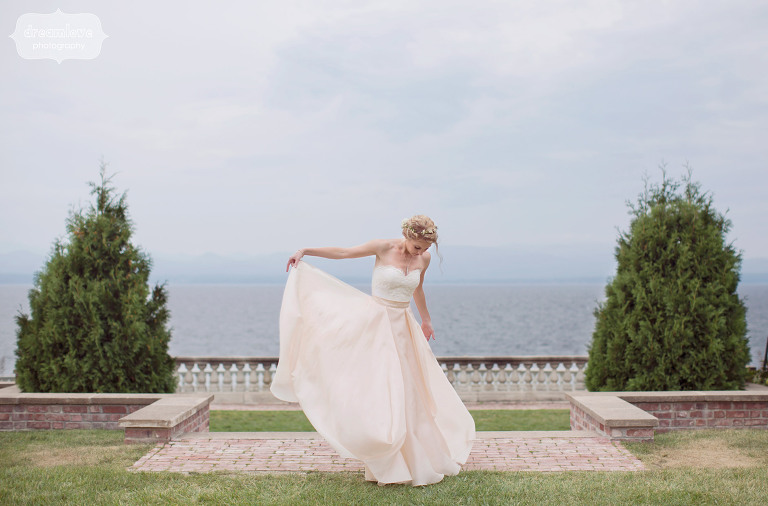 ethereal wedding photography of the bride holding up her pink skirt wedding dress in shelburne falls garden with lake champlain behind her