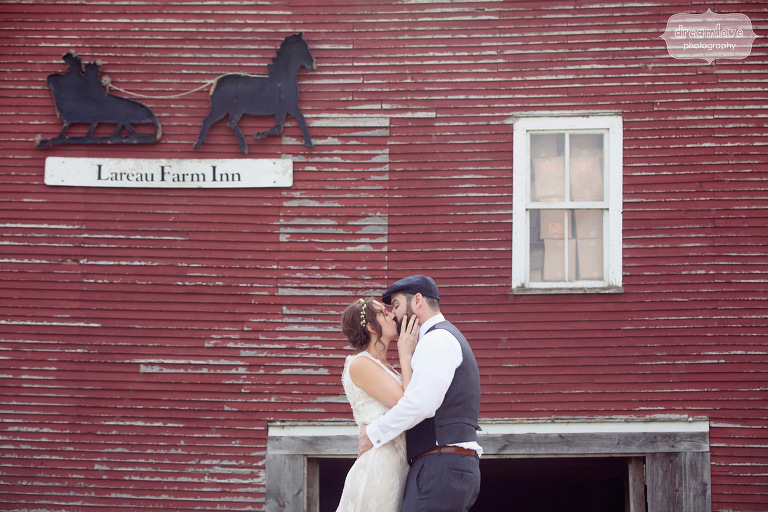 Bride and groom kissing in front of a red barn before their wedding at the Lareau Farm Inn in Waitsfield, Vermont.