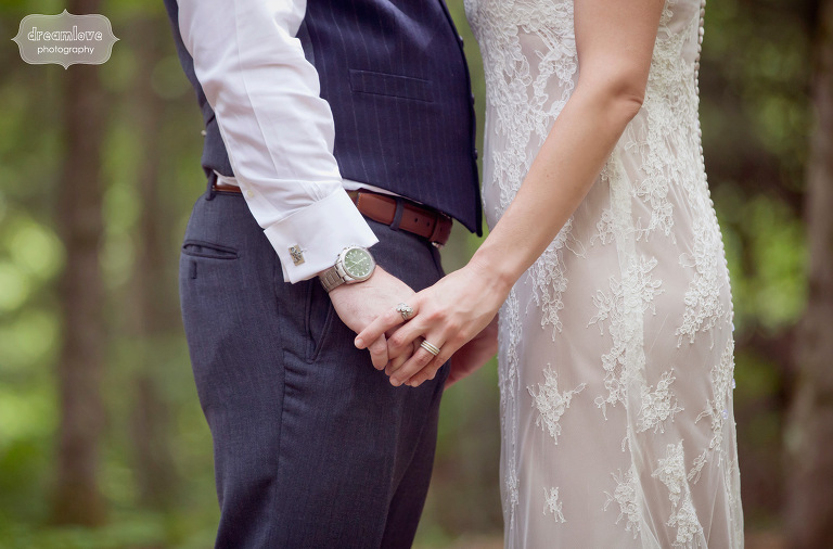 A detail photograph of a bride and groom holding hands in the Vermont woods.