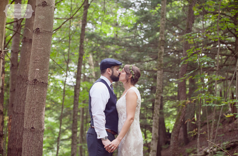 A bride and groom kissing amidst trees in a Vermont forrest.